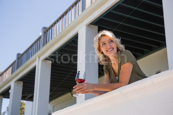 Mid adult woman looking away while holding red wine glass in balcony at restaurant Stock photo © wavebreak_media