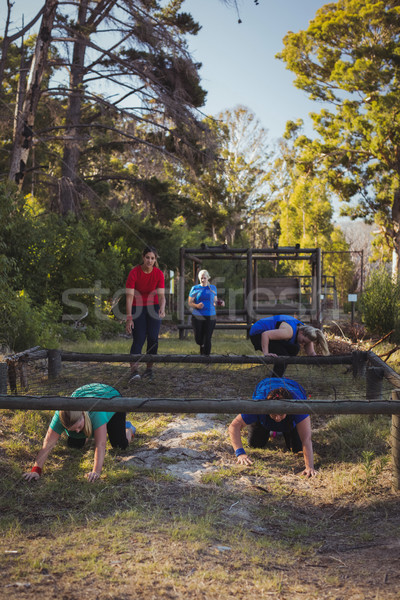 Group of fit women crawling under the net during obstacle course training Stock photo © wavebreak_media