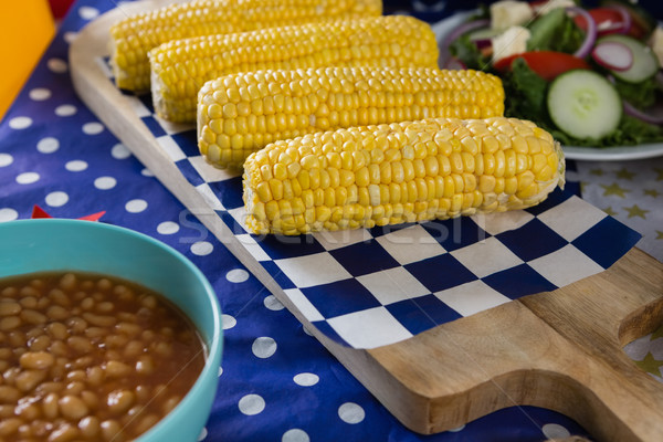 Stock photo: Baked beans and corn cob on wooden table with 4th july theme