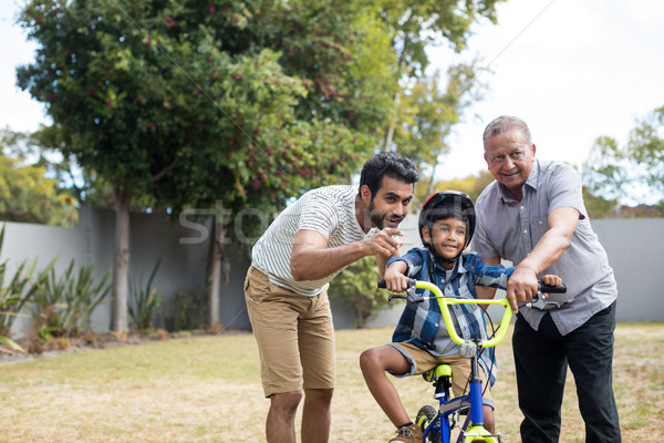 Stock photo: Boy learning bicycle with father and grandfather