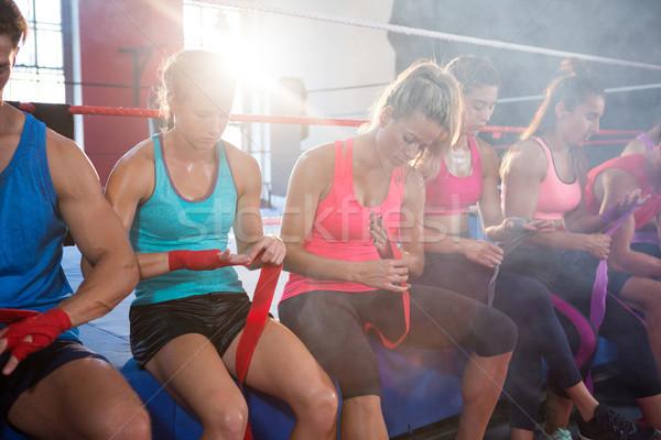 Back lit athletes sitting on boxing ring while wrapping bandages Stock photo © wavebreak_media