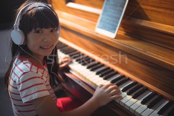 High angle portrait of girl wearing headphones while practicing piano Stock photo © wavebreak_media
