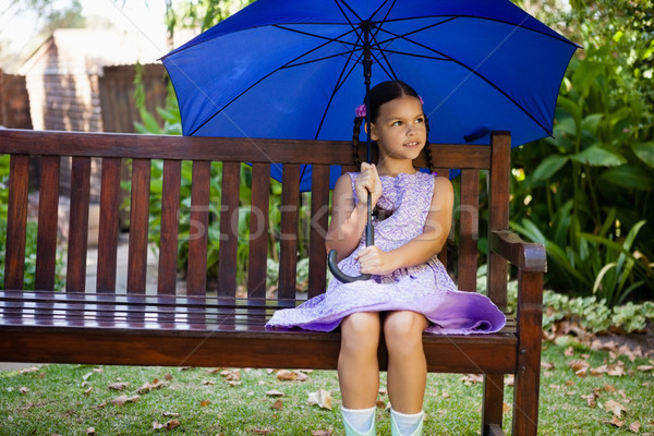 Girl sitting with blue umbrella on wooden bench Stock photo © wavebreak_media
