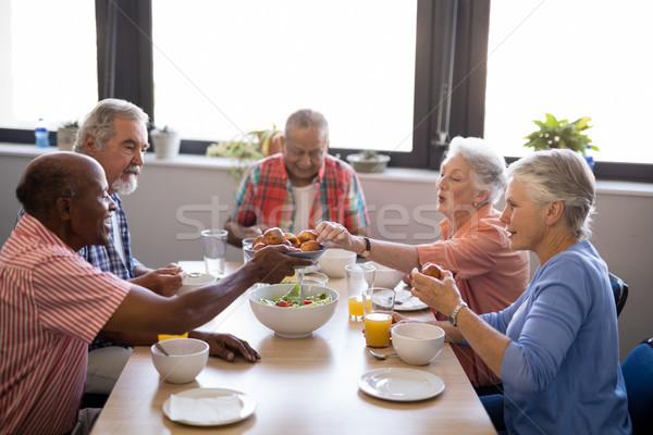Senior man giving food to friends sitting at table Stock photo © wavebreak_media