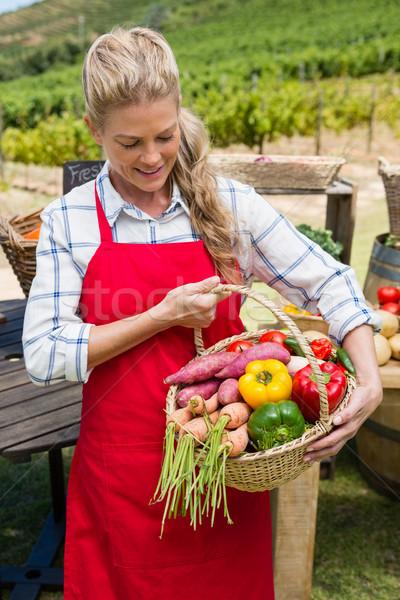 Woman holding a basket of fresh vegetables at stall Stock photo © wavebreak_media