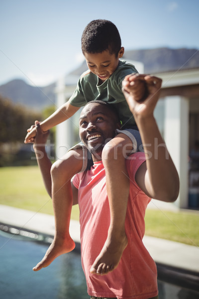 Father carrying son on shoulders near poolside Stock photo © wavebreak_media