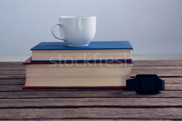 Livres tasse café puce regarder table en bois Photo stock © wavebreak_media