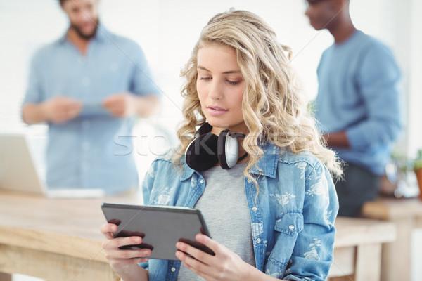 Happy woman with headphones while using digital tablet  Stock photo © wavebreak_media