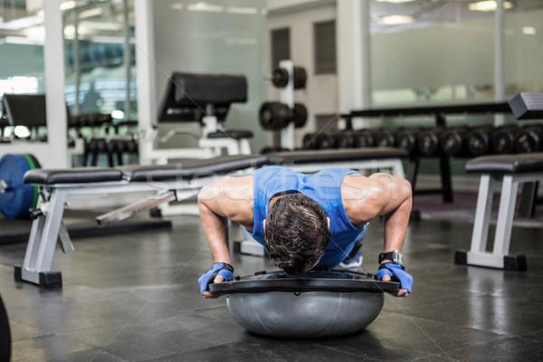 Muscular man doing push up with bosu ball Stock photo © wavebreak_media