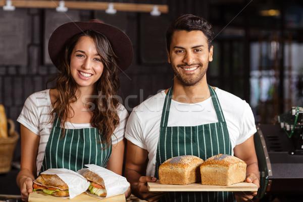 Smiling baristas holding bread and sandwiches Stock photo © wavebreak_media