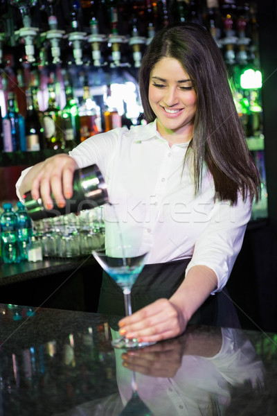 Pretty bartender pouring a blue martini drink in the glass Stock photo © wavebreak_media