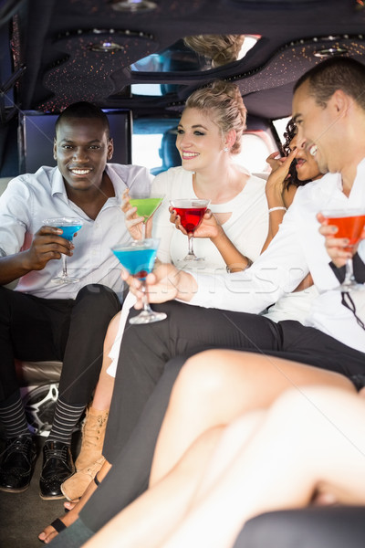 Stock photo: Well dressed people drinking cocktails in a limousine
