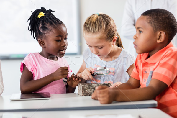 Stock photo: Pupils looking at rock with magnifying glass