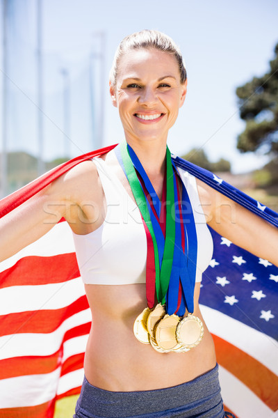 Portrait of happy female athlete holding up american flag with g Stock photo © wavebreak_media