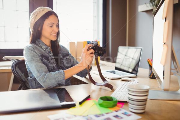 Graphic designer looking at pictures in digital camera Stock photo © wavebreak_media