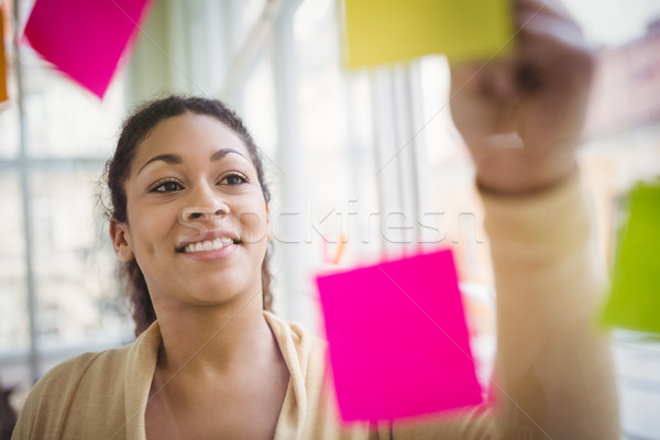 Young businesswoman smiling while writing on adhesive notes Stock photo © wavebreak_media