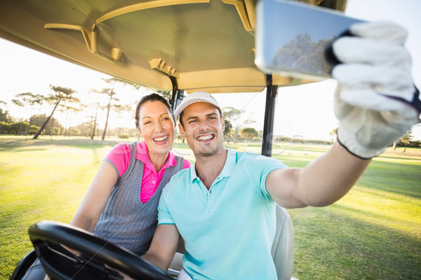 Golfer couple taking selfie while sitting in golf buggy Stock photo © wavebreak_media