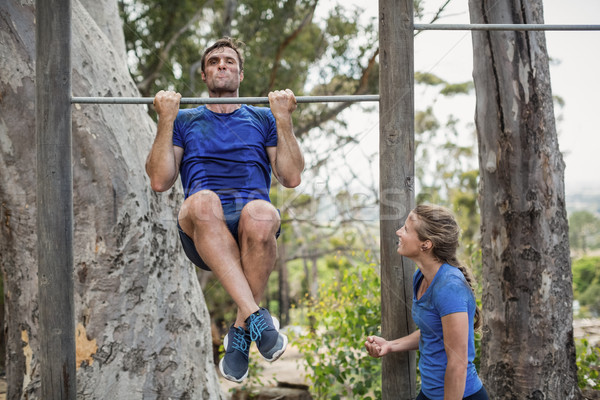 Fit man and woman performing pull-ups on bar during obstacle course Stock photo © wavebreak_media