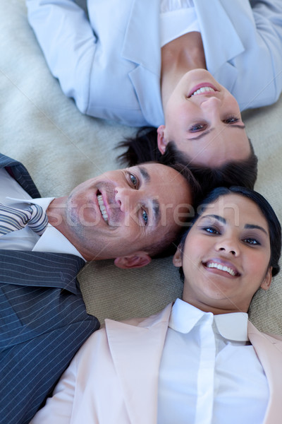 Business team on floor with heads together smiling Stock photo © wavebreak_media