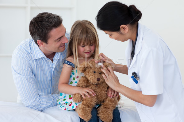 Portrait of a doctor and little girl examing a teddy bear Stock photo © wavebreak_media