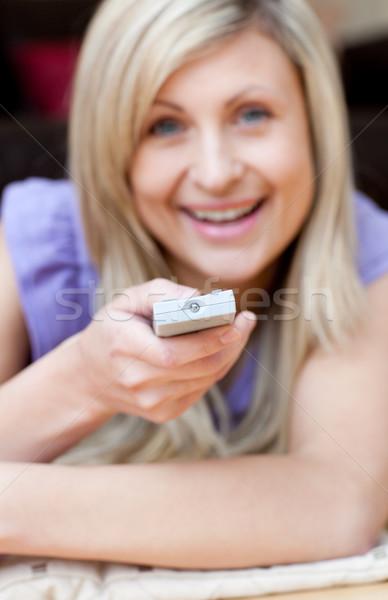Happy woman watching TV lying on the floor Stock photo © wavebreak_media