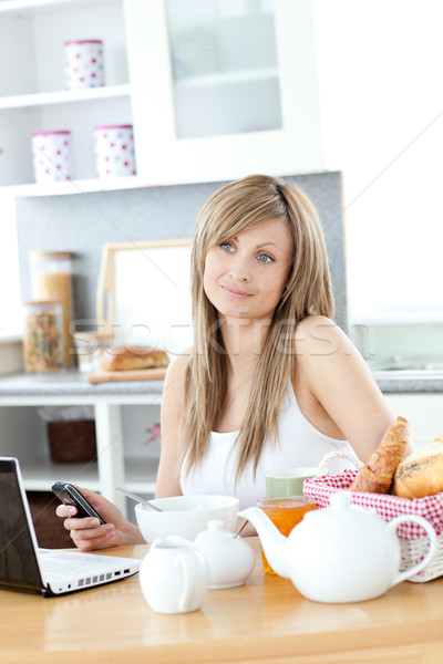 Cheerful woman using a phone and laptop in the kitchen Stock photo © wavebreak_media