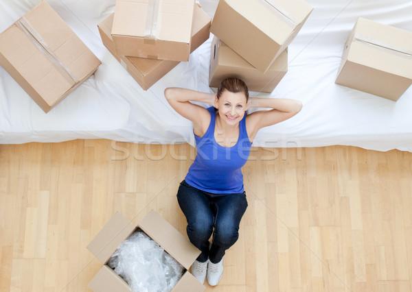 Beautiful woman sitting between boxes at home Stock photo © wavebreak_media