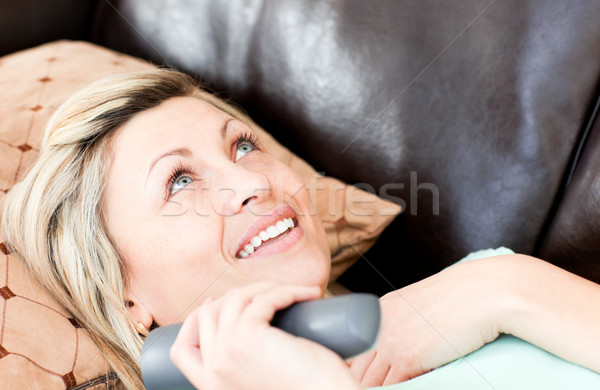 Lively woman using a remote  Stock photo © wavebreak_media