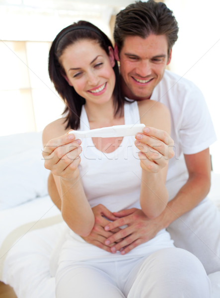 Smiling couple finding out results of a pregnancy test sitting on  bed Stock photo © wavebreak_media