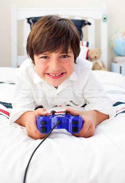 Happy boy playing video games in his bedroom Stock photo © wavebreak_media