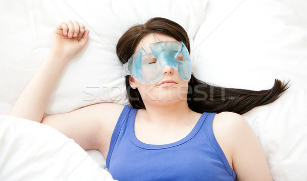 Caucasian young woman sleeping with an eye mask lying on a bed Stock photo © wavebreak_media