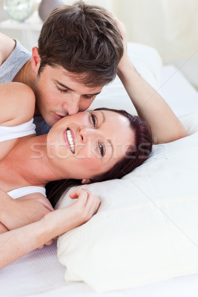 Loving caucasian couple lying on bed in the bedroom at home Stock photo © wavebreak_media