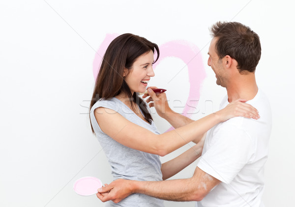 Happy woman hugging her boyfriend after drawing a heart on the wall Stock photo © wavebreak_media