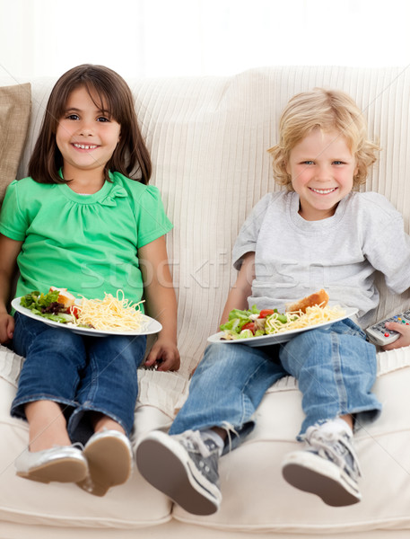Happy brother and sister watching television while eating pasta and salad on the sofa Stock photo © wavebreak_media