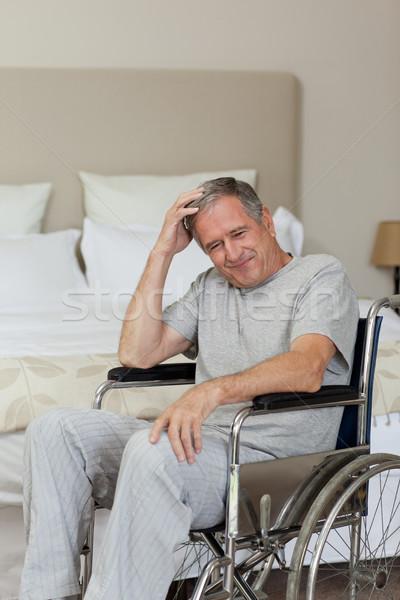 Smiling senior man in his wheelchair at home Stock photo © wavebreak_media