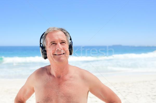 Retired man listening to some music on the beach Stock photo © wavebreak_media