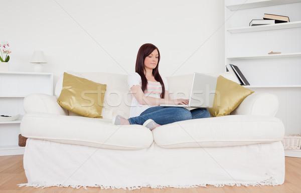 Bastante mujer relajante portátil sesión sofá Foto stock © wavebreak_media