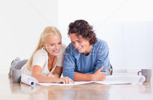 Smiling couple getting ready to move in a new house while lying on the floor Stock photo © wavebreak_media