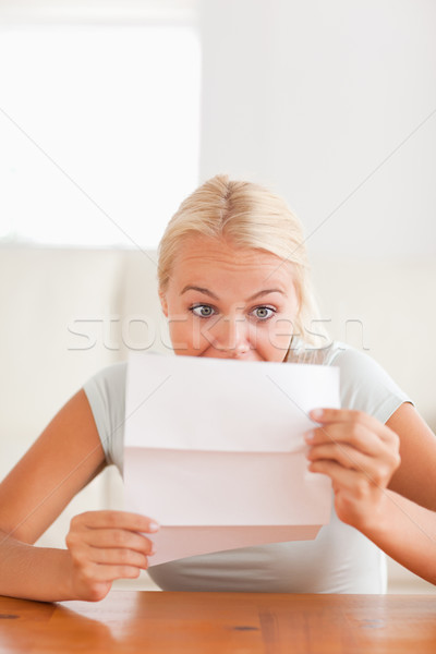 Woman looking at a letter in disbelief in her living room Stock photo © wavebreak_media