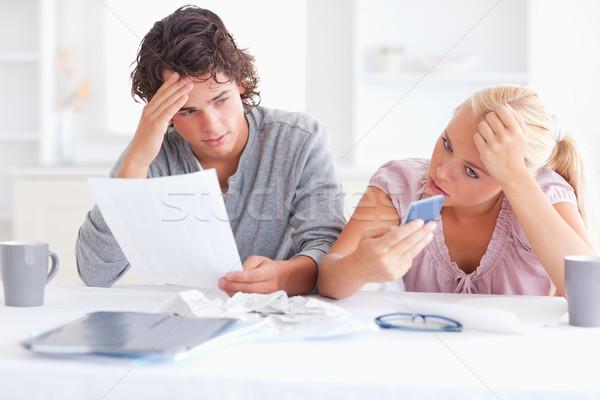 Unhappy couple doing accounts in their living room Stock photo © wavebreak_media