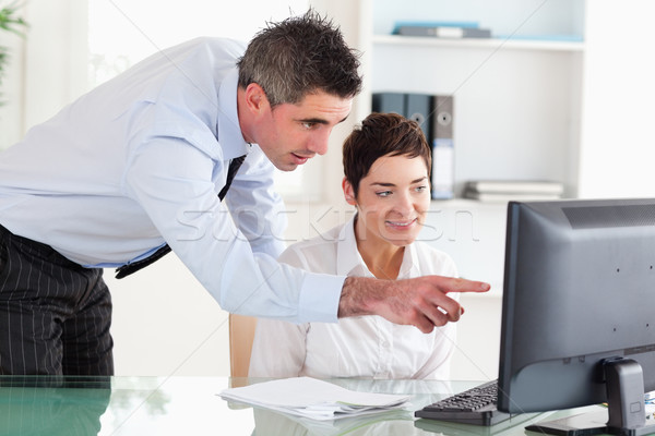 Businessman pointing at something on a screen to his secretary in an office Stock photo © wavebreak_media
