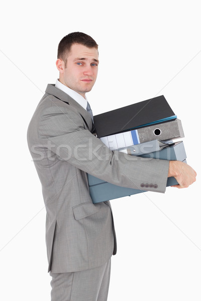 Stock photo: Portrait of a stressed businessman holding a stack of binders against a white background