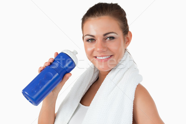 Smiling female with her bottle after workout against a white background Stock photo © wavebreak_media