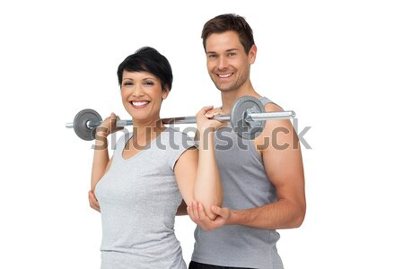 Young man helping a smiling woman to work out against a white background Stock photo © wavebreak_media