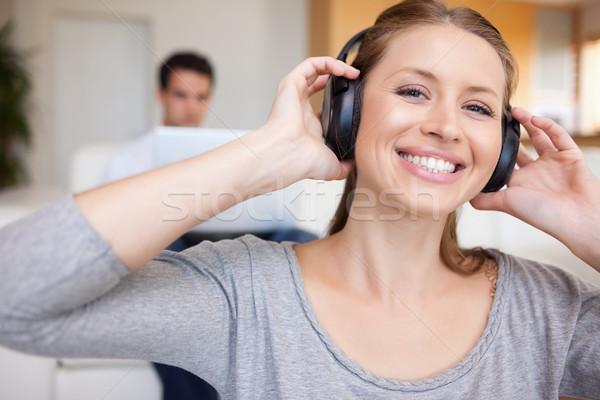 Zdjęcia stock: Uśmiechnięta · kobieta · słuchawki · człowiek · posiedzenia · za · sofa