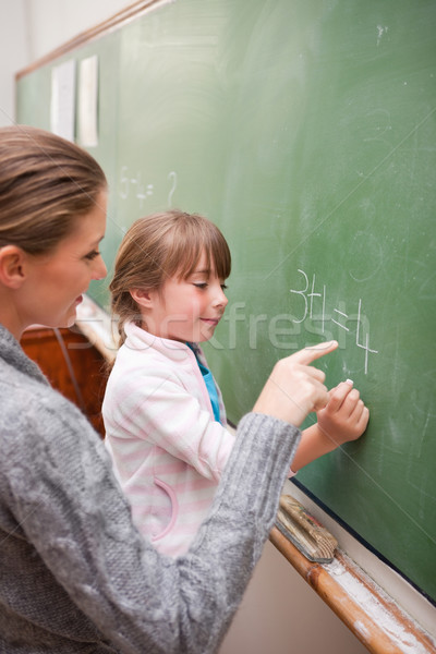 Portrait of a teacher and a pupil making an addition on a blackboard Stock photo © wavebreak_media
