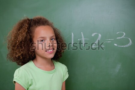 Cute schoolgirl pointing at an addition on a blackboard Stock photo © wavebreak_media