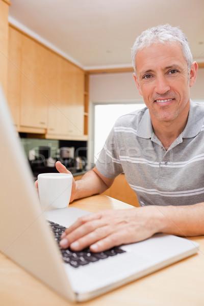 портрет человека ноутбук питьевой чай кухне Сток-фото © wavebreak_media