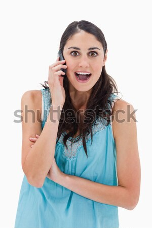 Portrait of an amazed woman making a phone call against a white background Stock photo © wavebreak_media