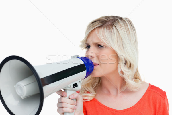 Young blonde woman speaking into a megaphone against a white background Stock photo © wavebreak_media